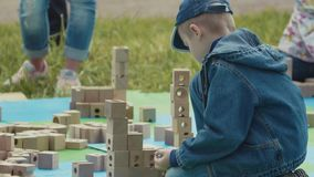 Little boy playing with wooden bricks and marble ball outdoor at city park stock footage