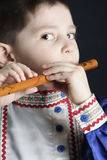 Little boy playing wooden flute Stock Photography