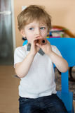 Little boy playing wooden flute indoor Stock Photos