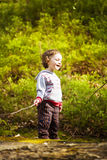 A little boy playing in the woods. Stock Image
