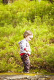 A little boy playing in the woods. Royalty Free Stock Image