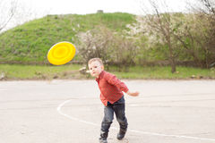 Little boy playing with a yellow frisbee Stock Photography