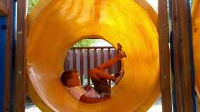 Little boy playing in a yellow tube in park stock video footage