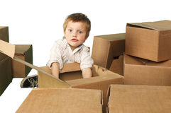 Little boy plays in boxes Stock Image