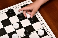 Little boy plays checkers Stock Photos