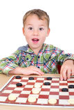Little boy plays checkers Stock Photo