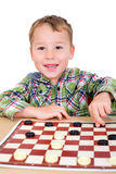 Little boy plays checkers Royalty Free Stock Photo