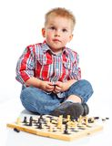 Little boy plays chess. Royalty Free Stock Images