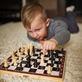 Little boy plays chess lying on floor royalty free stock images