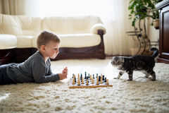 Little boy plays chess lying on floor royalty free stock photography