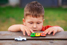 Little boy plays with colorful toy cars. Royalty Free Stock Photo