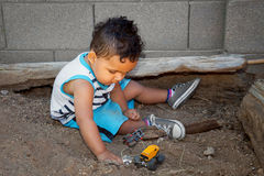 Little Boy Plays In Dirt. Little boy plays in the dirt with toy cars.  The ultimate playground for boys Royalty Free Stock Photo