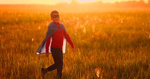 Little boy plays and dreams of a super hero at sunset. A boy dressed as a super hero standing in a mask and a red cloak runs laughing at the sunset in the summer stock footage