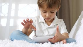 The little boy plays enthusiastically with the help of a tablet.