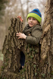 Little boy plays in forest, behind a large tree bark Stock Image
