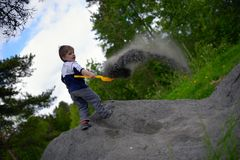Little boy plays on heap of crushed stone Royalty Free Stock Images