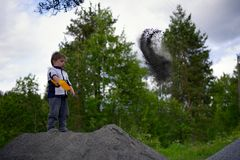 Little boy plays on heap of crushed stone Stock Photo