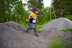 Little boy plays on heap of crushed stone Stock Images
