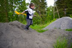 Little boy plays on heap of crushed stone Stock Image