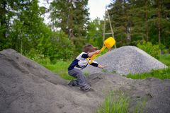 Little boy plays on heap of crushed stone Stock Photos