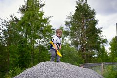Little boy plays on heap of crushed stone Royalty Free Stock Photo