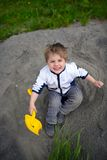 Little boy plays on heap of crushed stone Royalty Free Stock Image