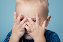 Little boy plays hide and seek Stock Image