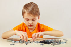 Little boy plays with mechanical kit at table Royalty Free Stock Image