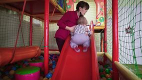 Cute little boy plays with mom in the playing room stock video