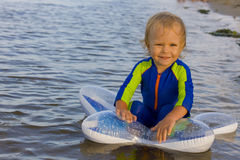 Little boy plays near water Stock Images