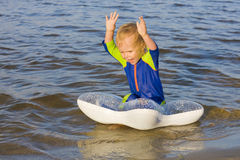 Little boy plays near the water Stock Images