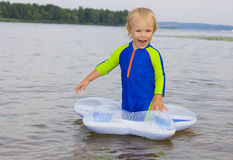 The little boy plays near water Royalty Free Stock Photos