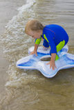 The little boy plays near water Stock Photography