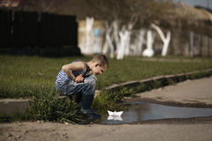 Little boy plays with paper boats in puddle Royalty Free Stock Photos