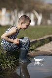 Little boy plays with paper boats in puddle Royalty Free Stock Photography