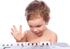 Little boy plays piano. Isolated on white Stock Photo
