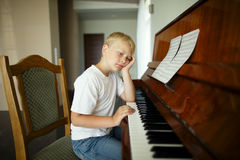 Little boy plays piano stock images