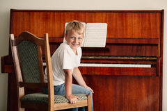 Little boy plays piano at home Stock Photos