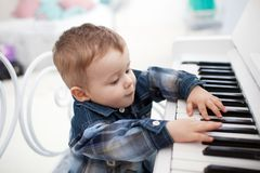 Little boy plays a piano. New Year concept stock images