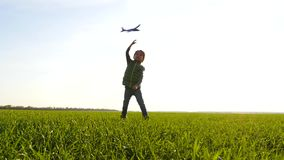 A little boy plays with a plane, running through a green meadow and launching it into the sky. Happy child.