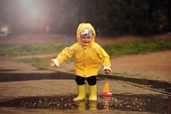 Happy child is playing in a puddle on a summer rainy day. a boy in a yellow raincoat walks in the park. royalty free stock photos