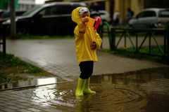 Little boy plays with a plastic boat in a puddle on a rainy autumn day. stock images