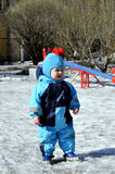 Little boy plays at playground in wintertime. On playground Royalty Free Stock Images