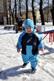 Little boy plays at playground in wintertime. On playground Royalty Free Stock Photo