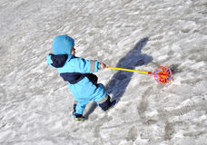 Little boy plays at playground in wintertime with toy. Little boy plays at playground in wintertime on playground with toy Royalty Free Stock Photos
