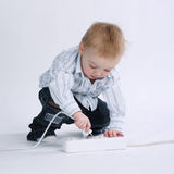 Little boy plays with plug Stock Images