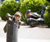Little boy plays with public fountain water in park Stock Image