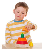 Little boy plays with a pyramid Stock Images
