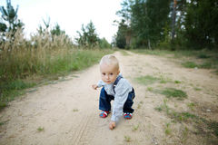 Little boy plays on the road Stock Images