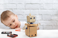 Little boy plays with the robot at home. Child exploring robot. Boy plays with the robot at home. Child exploring robot stock photo